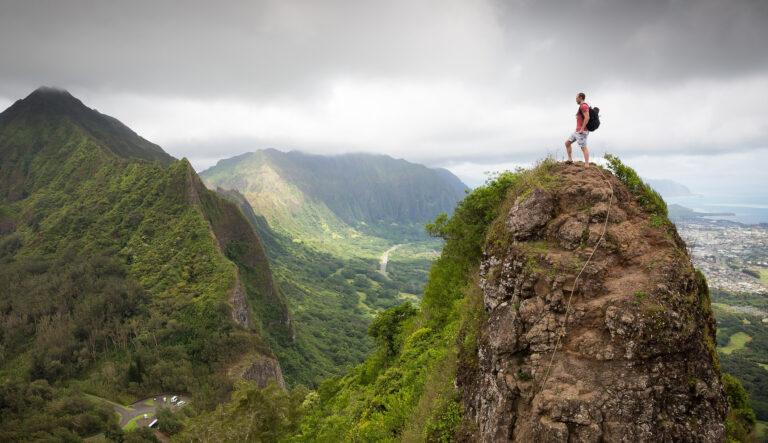 man climbing a steep mountain